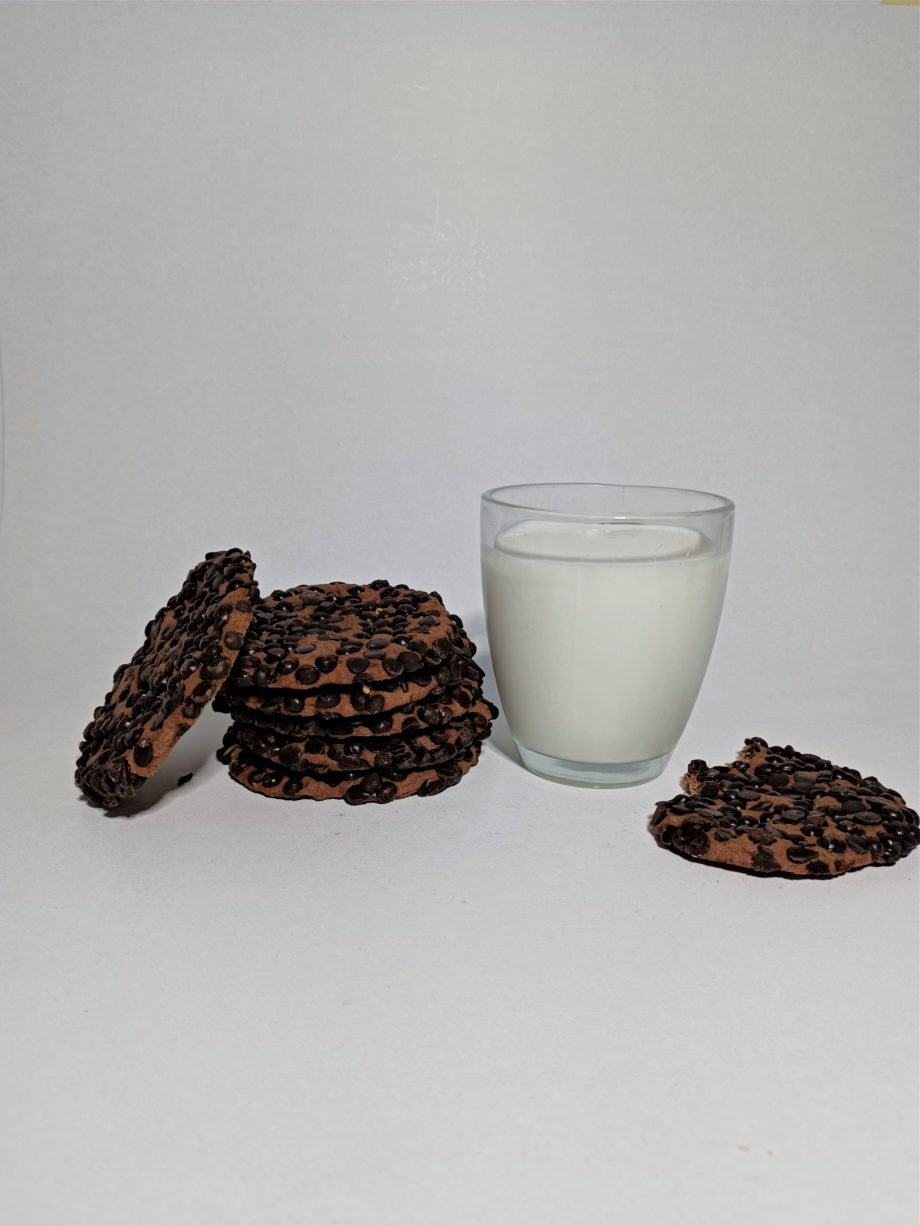 choco crisp cookies stack next to a cup of milk